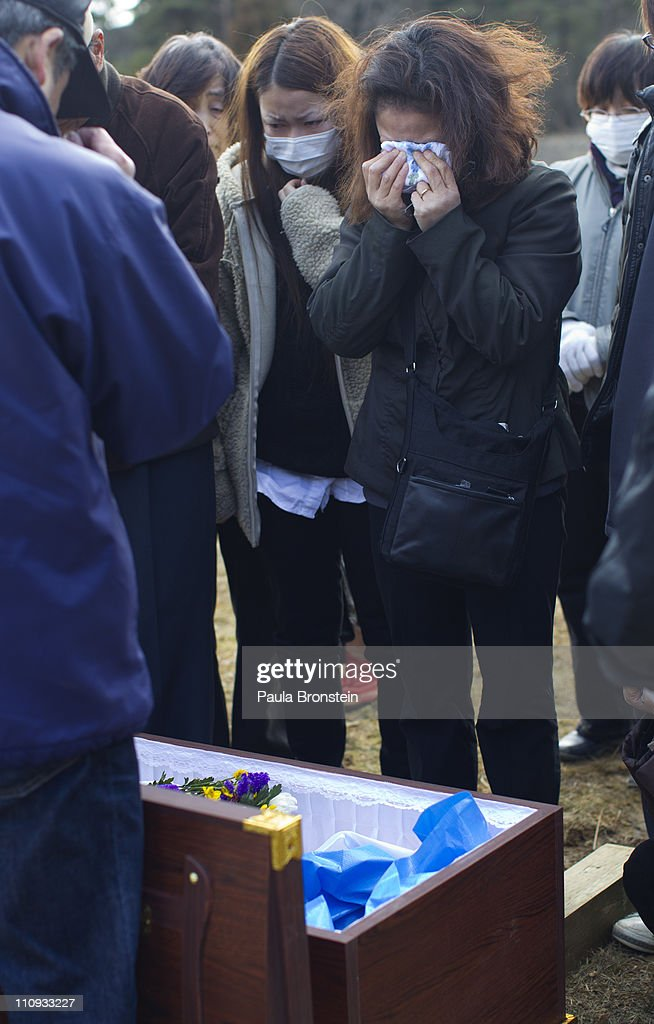 Family members grieve over the coffin of Masami Takahashi during a burial service at a temporary burial site March 27, 2011 in Kesennuma, Japan. Under Japanese Buddhist practice a cremation is the expected traditional way of dealing with the dead but now with the death toll so high crematoriums are overwhelmed and there is a shortage of fuel to burn them. Local municipalities are forced to dig mass graves as a temporary solution. More than two weeks after the magnitude 9 earthquake and tsunami struck Japan the death toll has risen to over 10,000 dead with still thousands missing and the expectation is that it will end up well over 20,000. Presently the country is still struggling to repair a damaged nuclear power plant that has caused tremendous problems, evacuations, and now tainted water supply in the Tokyo area causing more panic buying of bottled water.