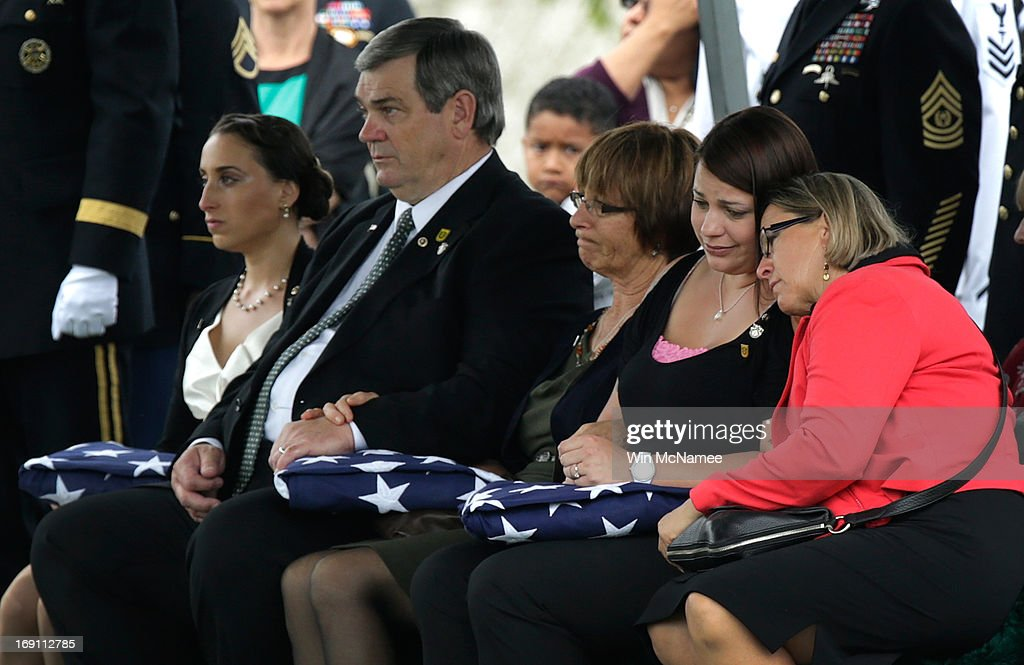 Family members hold American flags presented to them during the burial service for Sergeant First Class James F. Grissom at Arlington National Cemetery May 20, 2013 in Arlington, Virginia. From left to right are Angela Grissom, wife; James and Margery Grissom, parents; and Rebecca Grissom, sister. Grissom, from Hayward, California, died from wounds suffered in combat in Paktika province, Afghanistan.