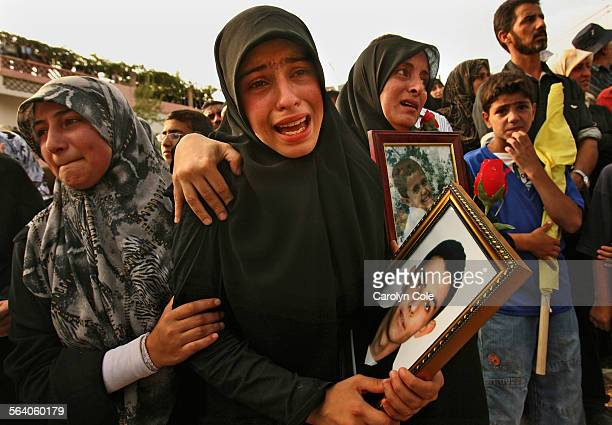 Family members hold photos of their loved ones who were killed in an Isareli bombing in the town of Qana on July 30th Twenty–nine victims were buried...