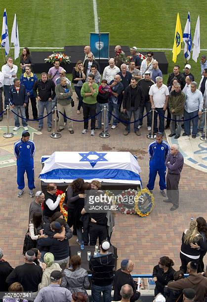 Family members hug close to the flag drapped coffin of football icon and former Liverpool player Avi Cohen as hundreds of fans gather at Tel Aviv's...