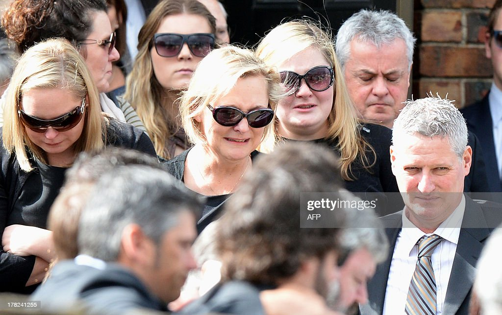 Family members, including mother Donna (C), of Australian baseball player Chris Lane, who was killed in the small Oklahoma town of Duncan in the US, leave St Therese's Parish after attending his funeral in Melbourne on August 28, 2013. Lane, 22, was in the US on a baseball scholarship and was jogging in Duncan when he was shot in the back and left to die on the side of the road on August 16. Two teenagers, aged 15 and 16, have been accused of shooting Lane, while a third, aged 17, was charged with use of a vehicle in the discharge of a weapon and acting as an accessory after the fact. AFP PHOTO / Mal Fairclough