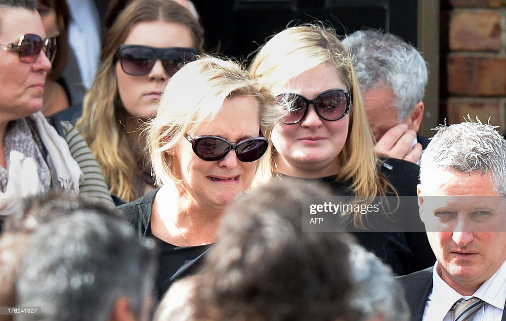 Family members, including mother Donna (centre L), of Australian baseball player Chris Lane, who was killed in the small Oklahoma town of Duncan in the US, leave St Therese's Parish after attending his funeral in Melbourne on August 28, 2013. Lane, 22, was in the US on a baseball scholarship and was jogging in Duncan when he was shot in the back and left to die on the side of the road on August 16. Two teenagers, aged 15 and 16, have been accused of shooting Lane, while a third, aged 17, was charged with use of a vehicle in the discharge of a weapon and acting as an accessory after the fact. AFP PHOTO / Mal Fairclough