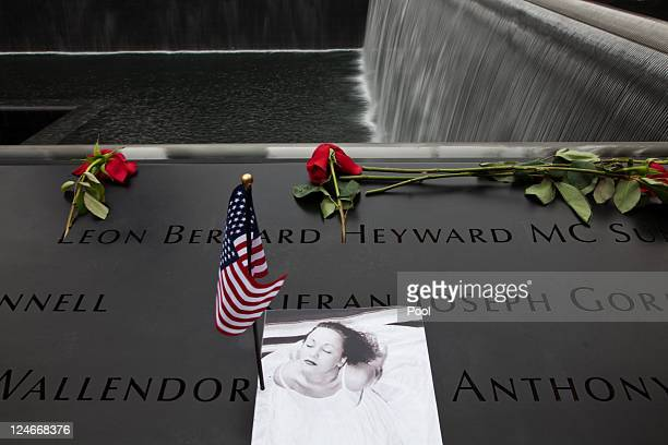 Family members leave flowers as they visit the south memorial pool during tenth anniversary ceremonies of the September 11 2001 terrorist attacks at...