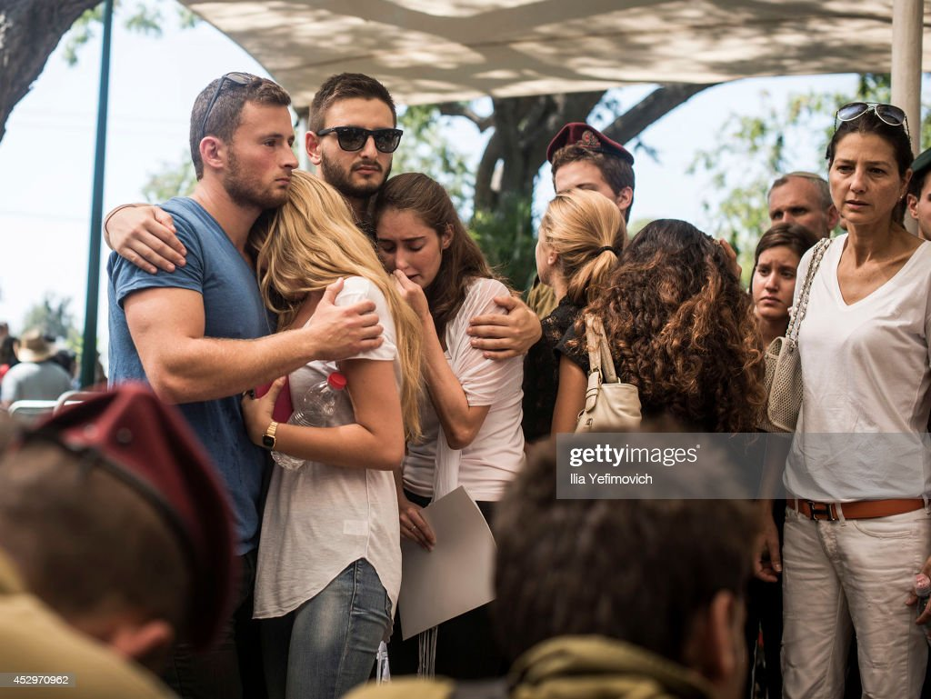 Family members mourn by the grave during the funeral of Staff Sgt. Guy Algranati on July 31, 2014 in Tel Aviv, Israel. Since the beginning of Operation Protective Edge in Gaza, more than 50 Israeli soldiers have been killed along with over 1000 Palestinians.