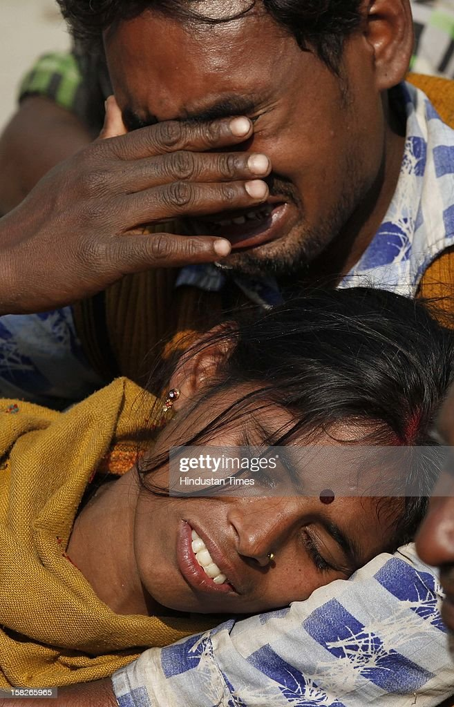 Family members mourn over death of their daughter Kanchaan, 9 after a wall collapsed at Dallupura village near New Ashok Nagar on December 12, 2012 in New Delhi, India. 5 children died and one got seriously injured in the incident.