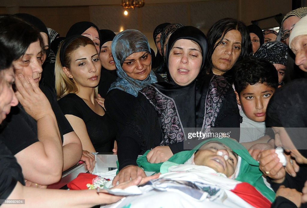 Family members mourn over the body of killed Lebanese soldier Ali Adnan Mounzer in his hometown of Rayak in the Bekaa valley, on May 28, 2013. Three Lebanese soldiers were killed overnight by a group of gunmen in in Wadi Hmayyed-Arsal near the Syrian border, the army said in the deadliest such attack since the start of the Syrian uprising. AFP PHOTO/STR