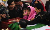 Family members mourn over the coffin of slain minister Shahbaz Bhatti during the funeral at the Fatima Church in Islamabad on March 4 2011...