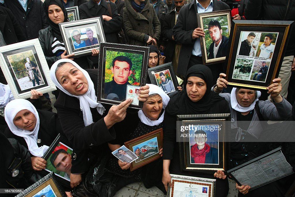 Family members of 34 Turkish Kurdish civilians, who were killed in December 2011 in Uludere at the Turkey-Iraq border by Turkish military jets that mistook the group for Kurdish rebels based in Iraq, hold on March 28, 2013 pictures of the victims during a protest outside the Turkish Parliament in Ankara. A recent parliamentary report on the massacre concluded that the Turkish military's air strike was not deliberate. AFP PHOTO/ ADEM ALTAN