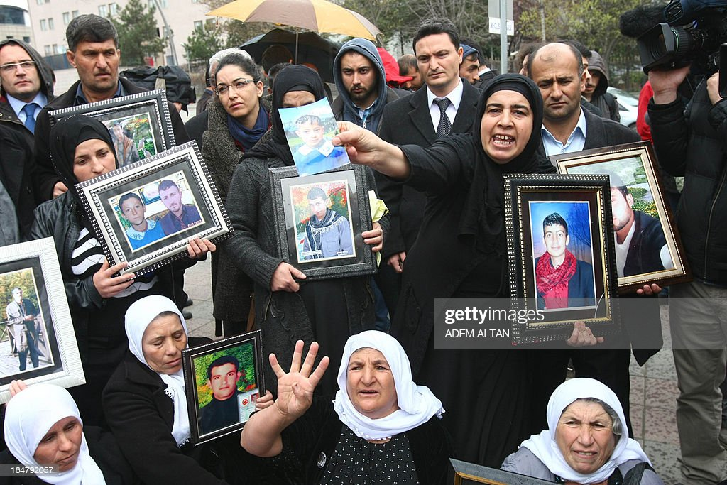 Family members of 34 Turkish Kurdish civilians, who were killed in December 2011 in Uludere at the Turkey-Iraq border by Turkish military jets that mistook the group for Kurdish rebels based in Iraq, hold on March 28, 2013 pictures of the victims during a protest outside the Turkish Parliament in Ankara. A recent parliamentary report on the massacre concluded that the Turkish military's air strike was not deliberate.