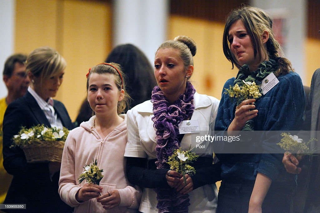 Family members of a victim of the Bali bombing place a flower at a wreath during the National Memorial Service in the Great Hall at Parliament House to mark the 10th anniversary of the terrorist attacks, on October 12, 2012 in Canberra, Australia. The ceremony marks tenth anniversary of the 2002 Bali suicide bombs that killed 202 people including 88 Australians.