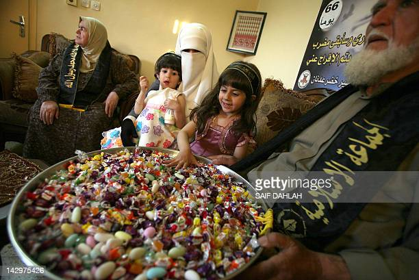 Family members of Adnan Khader distribute sweets at his family home in the northern West Bank village of Araba near Jenin on April 16 2012 in...