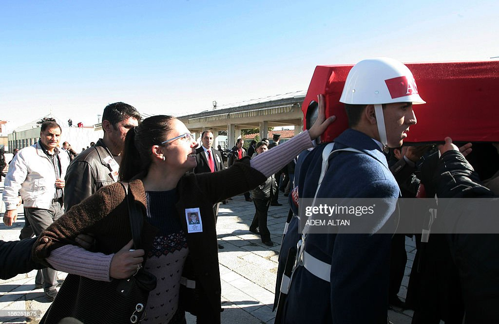 Family members of army officer Yakup Cinar, one of 17 Turkish soldiers who were killed in a helicopter crash early on November 9, 2012 in Siirt province, touch his coffin during his funeral in Ankara on November 12, 2012. The Turkish military helicopter crashed on November 9, 2012 in bad weather in the southeastern city of Siirt, killing all 17 troops on board, local officials said.