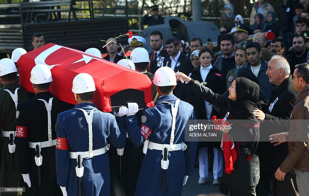 Family members of army officer Yakup Cinar, one of 17 Turkish soldiers who were killed in a helicopter crash early on November 9, 2012 in Siirt province, wave as soldiers carry his coffin during his funeral in Ankara on November 12, 2012. The Turkish military helicopter crashed on November 9, 2012 in bad weather in the southeastern city of Siirt, killing all 17 troops on board, local officials said. AFP PHOTO/ADEM ALTAN