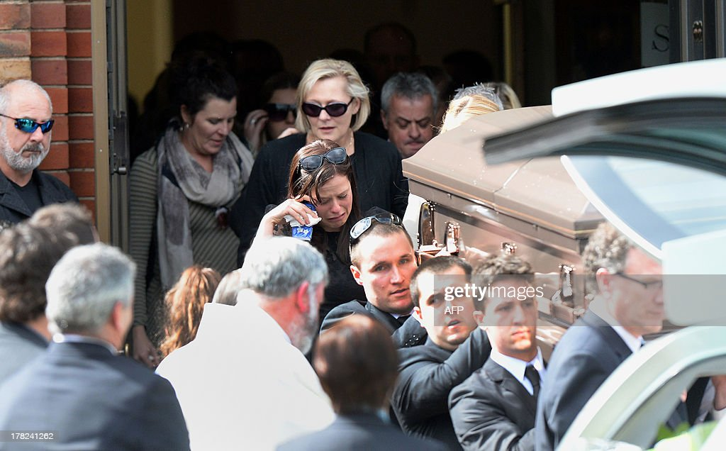 Family members (C) of Australian baseball player Chris Lane, who was killed in the small Oklahoma town of Duncan, follow as his coffin (R) is carried out of St Therese's Parish after his funeral in Melbourne on August 28, 2013. Lane, 22, was in the US on a baseball scholarship and was jogging in Duncan when he was shot in the back and left to die on the side of the road on August 16. Two teenagers, aged 15 and 16, have been accused of shooting Lane, while a third, aged 17, was charged with use of a vehicle in the discharge of a weapon and acting as an accessory after the fact. AFP PHOTO / Mal Fairclough