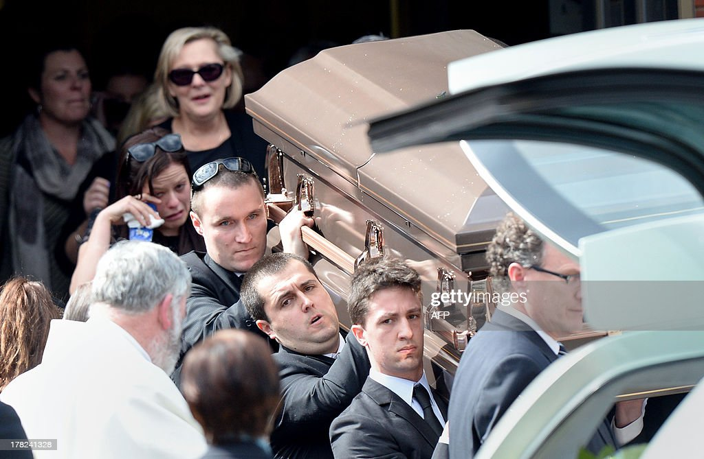 Family members (C) of Australian baseball player Chris Lane, who was killed in the small Oklahoma town of Duncan in the US, follow as his coffin (R) is carried out of St Therese's Parish after his funeral in Melbourne on August 28, 2013. Lane, 22, was in the US on a baseball scholarship and was jogging in Duncan when he was shot in the back and left to die on the side of the road on August 16. Two teenagers, aged 15 and 16, have been accused of shooting Lane, while a third, aged 17, was charged with use of a vehicle in the discharge of a weapon and acting as an accessory after the fact. AFP PHOTO / Mal Fairclough