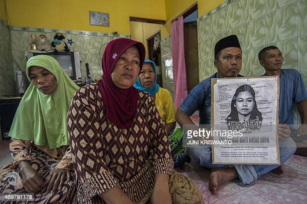 Family members of beheaded Indonesian maid Siti Zainab display a poster bearing her portrait at their family home in Bangkalan in East Java province...