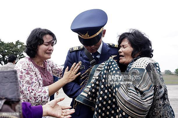 Family members of Captain Jan Hotlan Parlin Saragih cry on the arrival of his coffin on December 19 2016 in Medan Indonesia Captain Jan Hotlan Parlin...