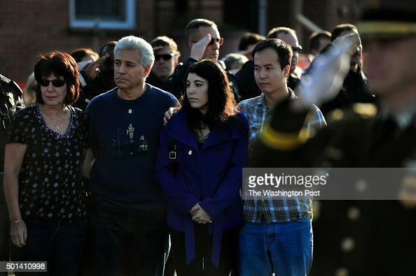 Family members of deceased police officer Noah Leotta wait to be greeted police officials who were exiting the motorcade that passed by in front of...
