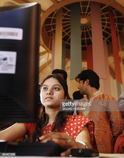 Family members of Indian stock traders watch as they trade during the special trading session on the occasion of Diwali the Festival of Lights inside...