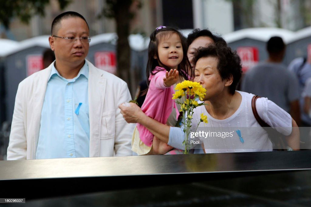 Family members of Ji Yao Justin Zhao pay their respect to him at the South Pool of the 9/11 Memorial during ceremonies for the twelfth anniversary of the terrorist attacks on lower Manhattan at the World Trade Center site on September 11, 2013 in New York City. The nation is commemorating the anniversary of the 2001 attacks which resulted in the deaths of nearly 3,000 people after two hijacked planes crashed into the World Trade Center, one into the Pentagon in Arlington, Virginia and one crash landed in Shanksville, Pennsylvania. Following the attacks in New York, the former location of the Twin Towers has been turned into the National September 11 Memorial & Museum.