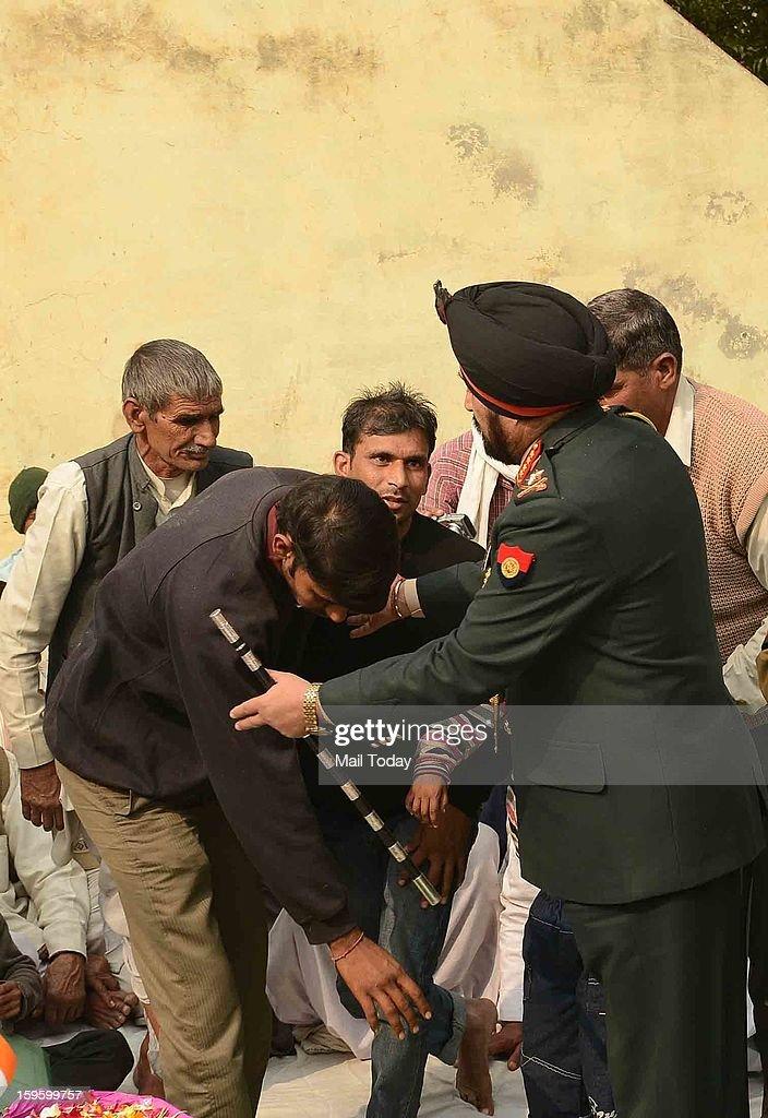 Family members of lance Naik Hemraj touches Army Chief Gen Bikram Singh's feet at village Shernagar near Mathura on Wednesday.