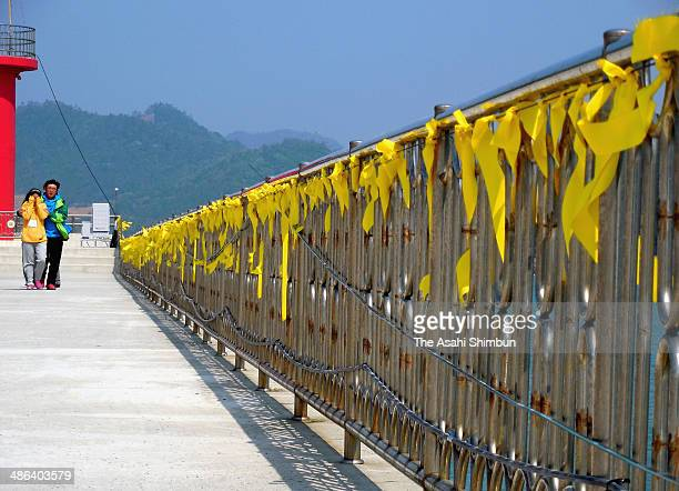 Family members of missing passengers walk next to the yellow ribbons hung in pray for the missing passengers of sunken ferry 'Sewol' at the fense of...