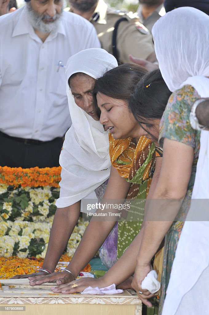 Family members of Sarabjit Singh wife Sukhpreet and daughters Swapandeep and Poonam mourning near his pyre during cremation ceremony at his native village Bikhiwind on May 3, 2013 about 40 Kms from Amritsar, India. Sarabjit Singh, an Indian prisoner in Pakistan who died after being brutally assaulted in a Pakistani jail, was cremated in his native village with full state honours .