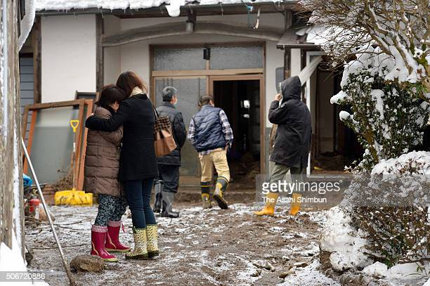 Family members of the 88yearold woman who was killed by a landslide stand outside the destroyed house after the snowstorm triggered a landslide on...