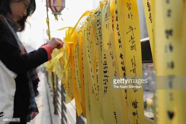 A family members of the missing passengers of sunken ferry 'Sewol' writes a message onto yellow ribbons on April 24 2014 in Seoul South Korea The...