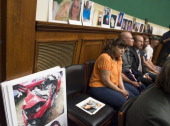 Family members of victims resulting from problems with GM ignition switches sit alongside their loved ones photographs as General Motors CEO Mary...