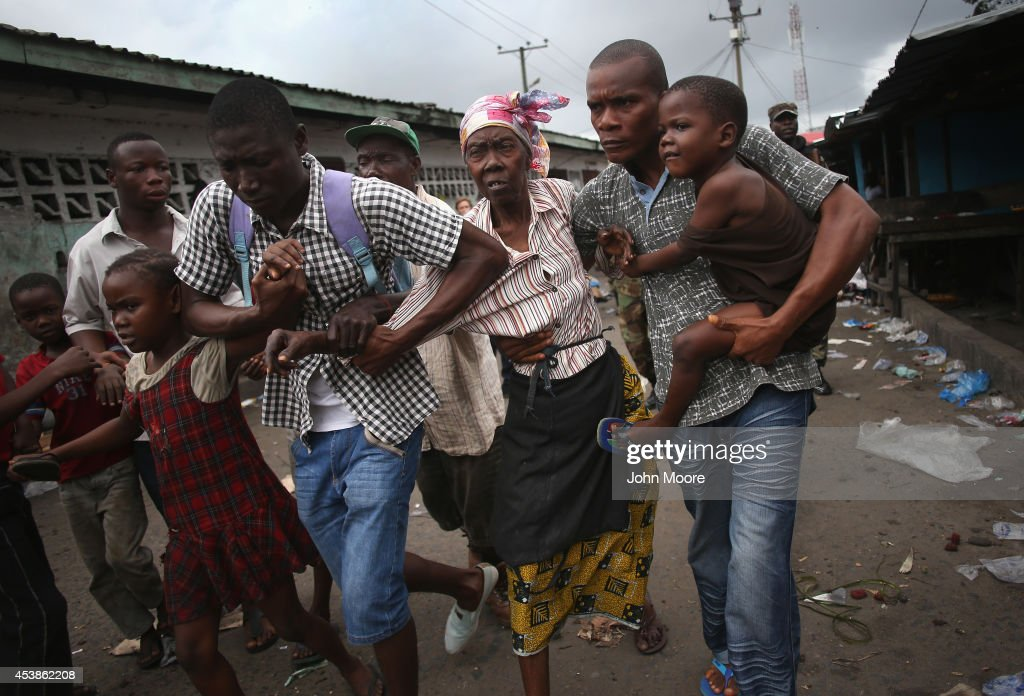 Family members of West Point district commissioner Miata Flowers flee the slum while being escorted by the Ebola Task Force on August 20 2014 in...