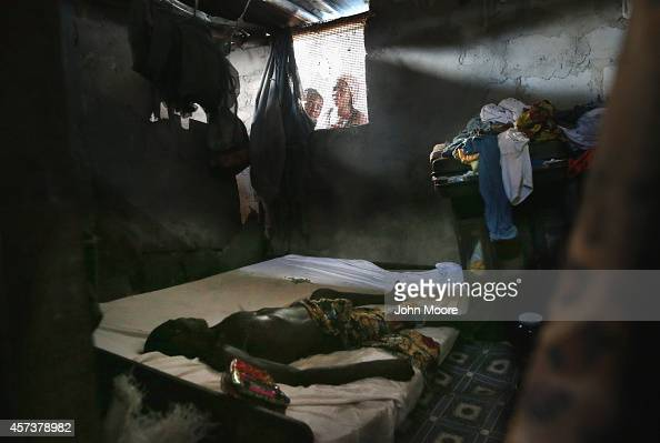Family members peer into a bedroom as the dead body of a man awaits the arrival of an Ebola burial team to take him for cremation on October 17 2014...