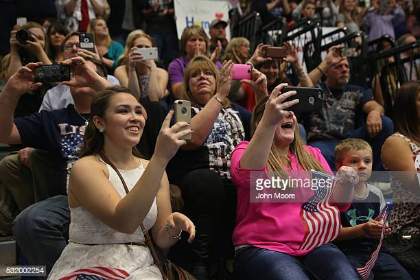 Family members photograph as their loved ones arrive to a welcome home ceremony for soldiers returning from Iraq on May 17 2016 at Fort Drum New York...