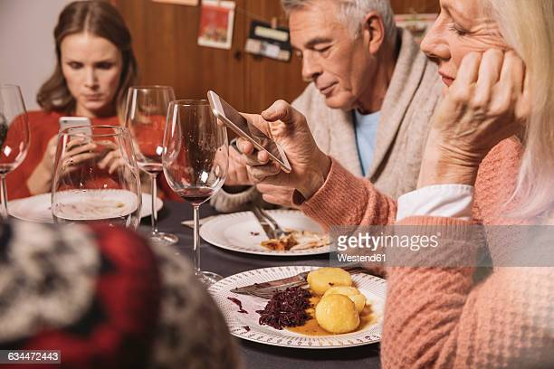 Family members playing with their smartphones after Christmas dinner