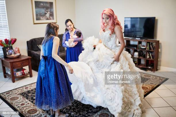 Family members preparing young womans quinceanera gown in living room
