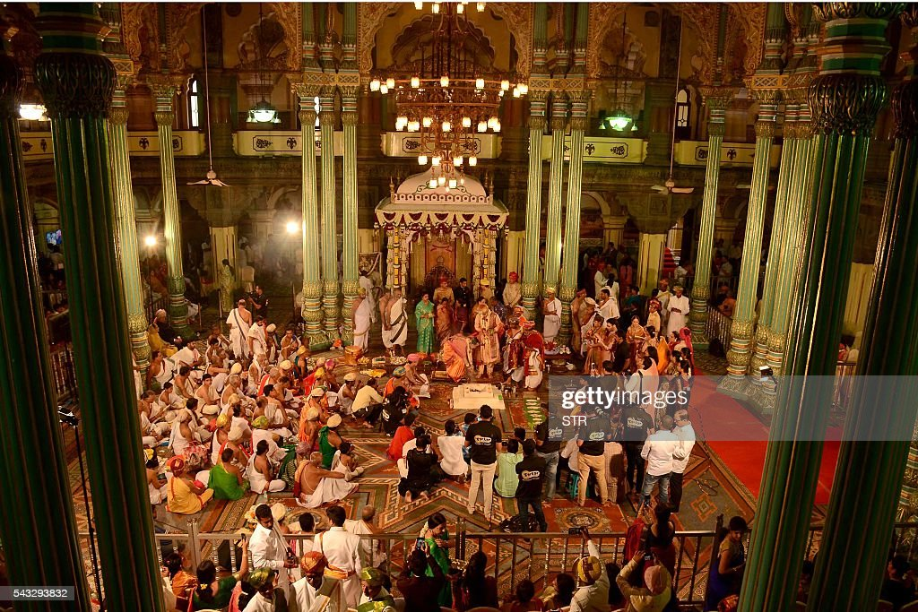Family members, relatives and friends attend the wedding of the 27th titular head of the Wodeyar dynasty, 24-year-old Yaduveer Chamraja Krishnadatta Wodeyar (CR) and Trishika Kumari (CL) of the Dungarpur dynasty of Rajasthan at the Amba Vilas Palace in southern Mysore city on June 27, 2016. The royal wedding which happened after four decades, began with invocations to the royal family deity Hindu Goddess Chamundeshwari, as per the Wodeyar's dynastic traditions. / AFP / STR