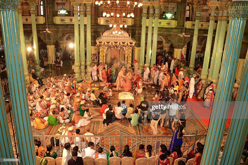 Family members, relatives and friends attend the wedding of the 27th titular head of the Wodeyar dynasty, 24-year-old Yaduveer Chamraja Krishnadatta Wodeyar (CL) and Trishika Kumari (CR) of the Dungarpur dynasty of Rajasthan at the Amba Vilas Palace in southern Mysore city on June 27, 2016. The royal wedding which happened after four decades, began with invocations to the royal family deity Hindu Goddess Chamundeshwari, as per the Wodeyar's dynastic traditions. / AFP / STR