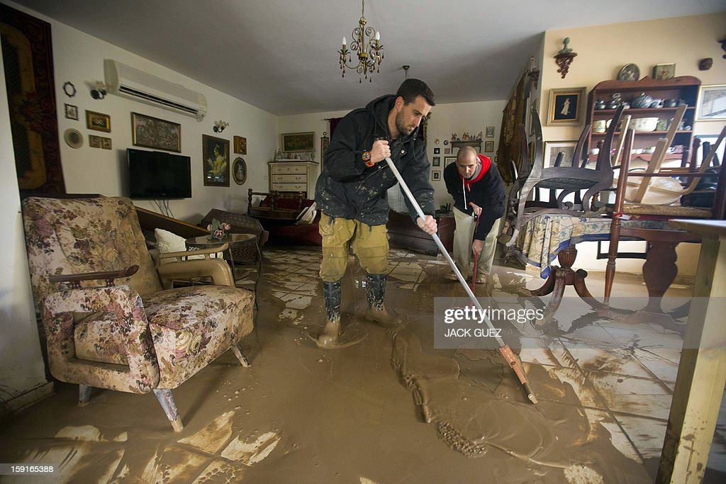 Family members sweep murky water from their flooded house in Beit Hefer near the Mediterranean coastal city of Netanya, north of Tel Aviv, on January 9, 2013, after heavy rains overnight. Israel and the Palestinian territories have been lashed by heavy rain and high winds since January 6, which has caused flooding across the region.