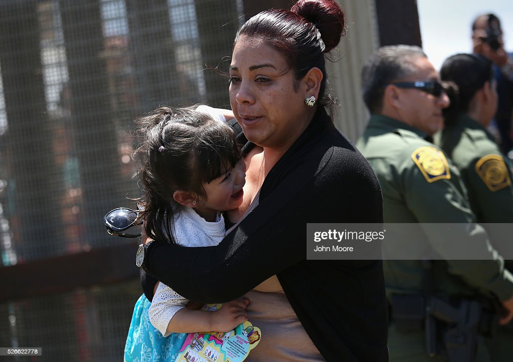 Family members walk away from the U.S.-Mexico Border fence after embracing loved ones during an 'Opening the Door of Hope' event on April 30, 2016 in San Diego, California. Five families, with some members living in Mexico and others in the United States, were permitted to meet and embrace for three minutes each at a door in the fence, which the U.S. Border Patrol opened to celebrate Mexican Children's Day. It was only the third time the fence, which separates San Diego from Tijuana, had been opened for families to briefly reunite. The event was planned by the immigrant advocacy group Border Angels.