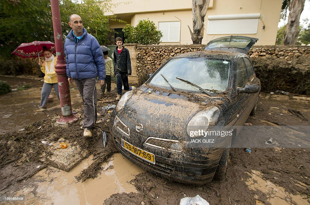 Family members walk next to to their damaged car covered in mud due to heavy rains overnight which caused flooding in Beit Hefer, near the Mediterranean coastal city of Netanya, north of Tel Aviv, on January 9, 2013. Israel and the Palestinian territories have been lashed by heavy rain and high winds since January 6, which has caused flooding across the region. AFP PHOTO / JACK GUEZ