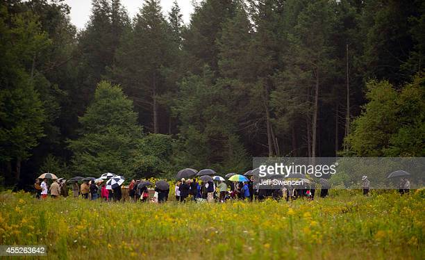 Family members walk through the rain to the impact site during 13th anniversary ceremonies commemorating the September 11th attacks near the Wall of...