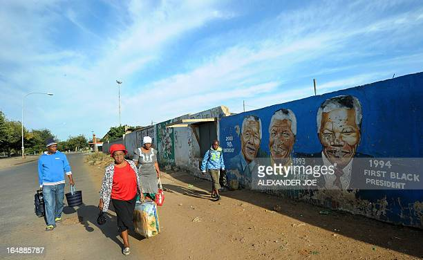 Family members walk to a bus stop in front of a wall bearing painted portraits of former South African President Nelson Mandela in Soweto on March 29...