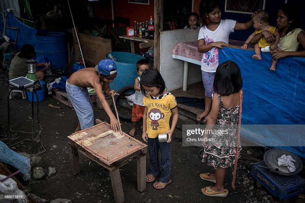 Family members watch on as a boy plays pool with marbles on a makeshift pool table in a temporary bunk house complex on April 16, 2014 in Tacloban, Leyte, Philippines. People continue to rebuild their lives five months after Typhoon Haiyan struck the coast on November 8, 2013, leaving more than 6000 dead and many more homeless. Although many businesses and services are functioning, electricity and housing continue to be the main issues, with many residents still living in temporary housing conditions due to 'No Build' areas preventing them from rebuilding their homes. This week marks Holy Week across the Philippines and will see many people attend religious activities.