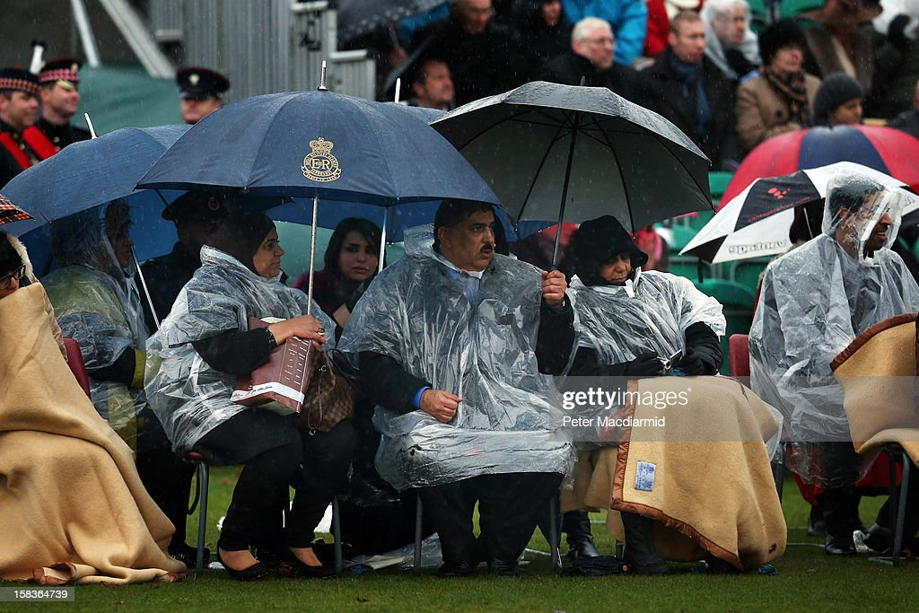 Family members watch the Sovereign's Parade in heavy rain at the Royal Military Academy at Sandhurst on December 14, 2012 in England. The parade marks the completion of 44 weeks of training for 200 young people who will be commissioned into the British Army and the armies of 13 overseas countries. Senior Under Officer Sarah Hunter-Choat became the fourth woman in the Royal Military Academy's history to receive the prestigious Sword of Honour which is awarded to the best Officer Cadet on the course.