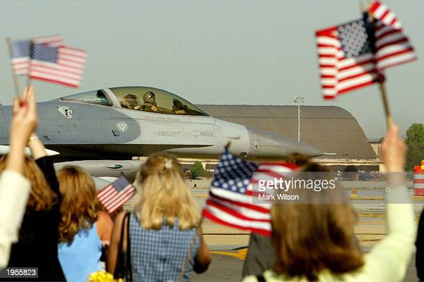 Family members wave US flags as an F16 fighter jet passes after landing at Andrews Air Force Base April 28 2003 in Camp Springs Maryland The US Air...