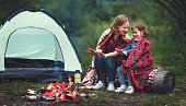Family mother and child daughter warm their hands by bonfire on  camping trip with a tent