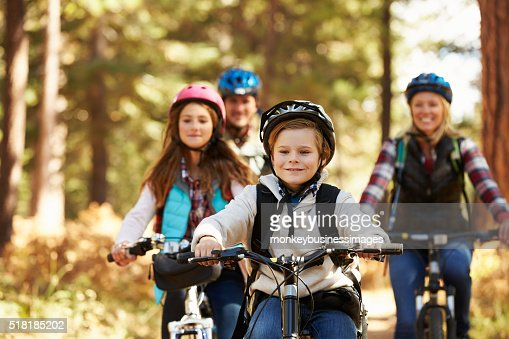 Family mountain biking on forest trail, front view, close-up : Stock Photo