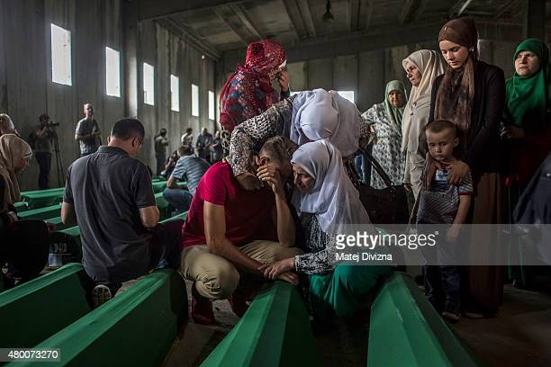 A family mourn over a coffin among 136 coffins of victims of the 1995 Srebrenica massacre in the hall at the Potocari cemetery and memorial near...