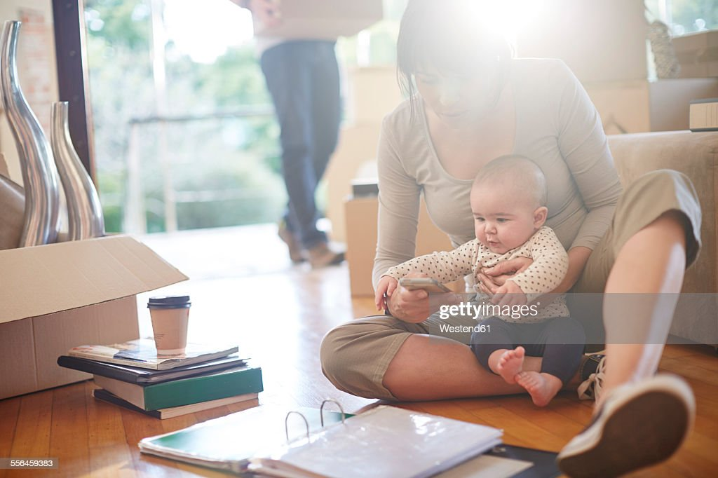 Family moving house, mother sitting with a baby