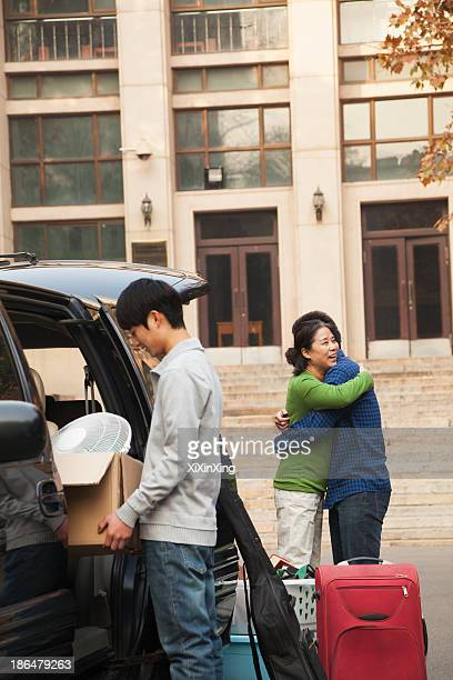 Family moving their son into dormitory on college campus